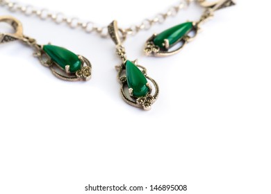 Necklace and earrings with natural green stones isolated on white background.