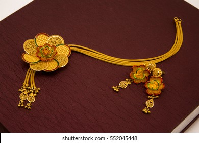 Necklace with floral design along with ear rings in brown texture.