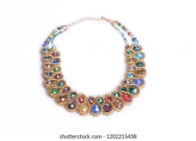 Necklace of gold chains, adorned with colorful beads. Female necklace on  a white background. A round gold metal necklace with blue, red, yellow, green, purple crystals. Bijouterie. Valuable Jewellery