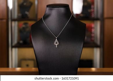 Necklace made of white gold with diamonds on a stand in fashion jewelry boutique. Black stand neck with luxury jewelry, women accessories in store window.