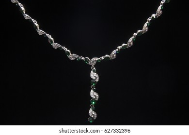 Necklace silvery metal with green stones on a black background