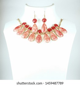 Necklace/neck piece and ear ring sets  made of colored stones on white mannequin in white copy space background. Indian jewelry