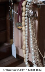 Necklaces hanging from the door of a jewlery box in an antique store