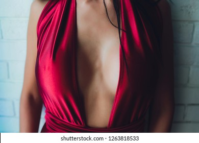 neckline, beautiful large female breast, red dress, close-up.