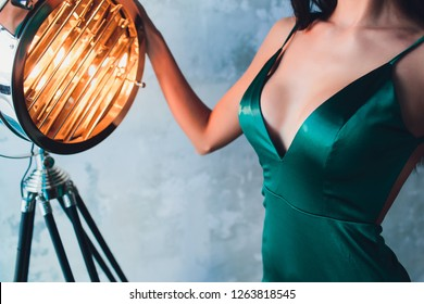 neckline, beautiful large female breast, green dress, close-up. aluminum cinema spotlight