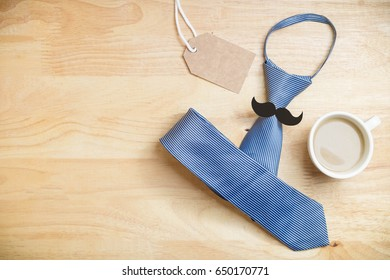 Necktie with mustache and coffee and paper craft tag card on wooden background, top view , Father 's Day concept