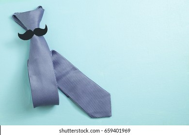 Necktie with mustache on blue background, top view , Father 's Day concept