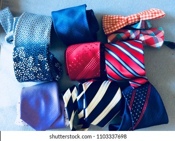 Neckties. Set different neckties. Colored tie for men. Set of stylish men accessories, men's fashion. Collection of coiled neckties in display. Sakura necktie. Bow tie.