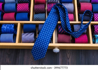 neckties showcase at store. Collection of coiled neckties in display and one flat necktie on top of others