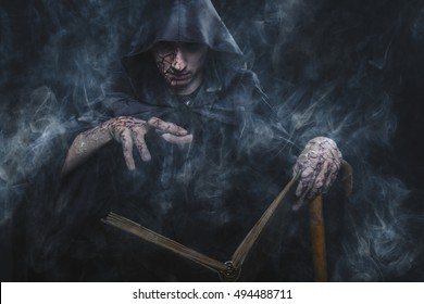 Necromancy sorcerer casting black magic spell using his book of shadows