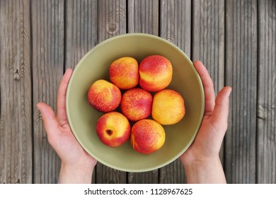 nectarines in the green plate. wooden background. nectarines in the hands.