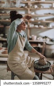 I need a break. Portrait of exhausted craftswoman closing eyes and touching forehead while sitting on bench pottery wheel and clay
