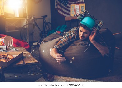 Need to delete that picture! Handsome young man in beer hat using his smart phone while lying on bean bag in messy room after party