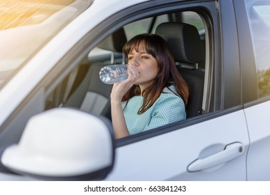 need to drink water every day, anywhere. beautiful brunette behind the wheel. drink driving.
