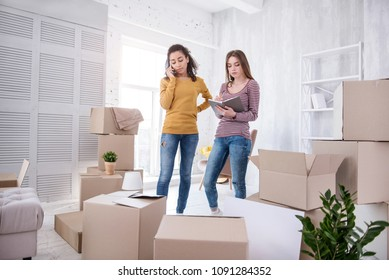 In need of help. Beautiful young girls contacting removers company while finishing up packing their belongings