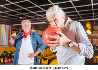I need luck. Serious aged man kissing the ball while preparing to throw it