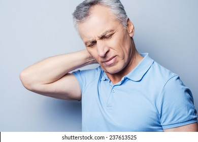 I need a massage. Frustrated senior man in T-shirt holding hand on his neck while standing against grey background