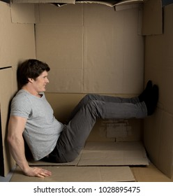 Need more space concept. Full length of young man is sitting in cardboard box while pushing the wall with his feet and trying to move them. He is expressing irritation
