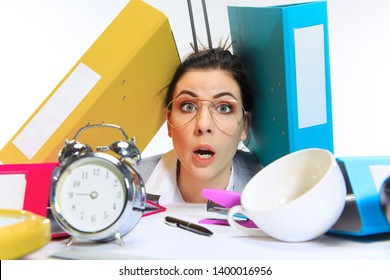 Need more time. Young woman getting a lot of work and deadline, being under the pressure of the deals. Pressed by folders with papers. Concept of office worker's troubles, business, problems and