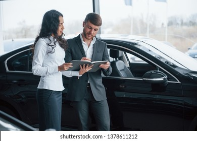 Need to sign in that document. Female customer and modern stylish bearded businessman in the automobile saloon.