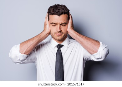 I need silence. Frustrated young man in shirt and tie covering ears with hands and keeping eyes closed while standing against grey background