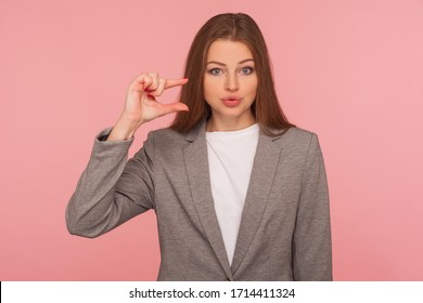 Need some more! Portrait of sceptic displeased young woman in business suit making a little bit gesture, small size, dissatisfied with low rating. indoor studio shot isolated on pink background