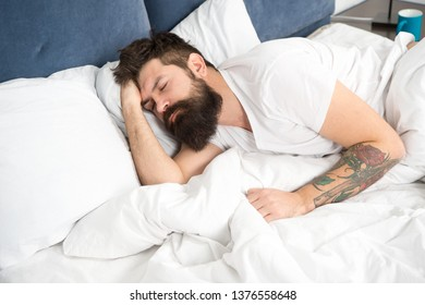 Need some rest. Sleep disorders concept. Man bearded hipster having problems with sleep. Guy lying in bed try to relax and fall asleep. Relaxation techniques. Violations of sleep and wakefulness.