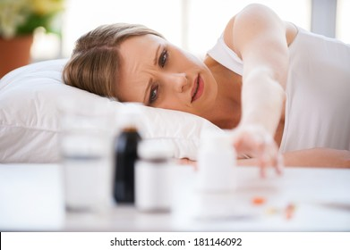 I need to take medicines. Young woman stretching out hand and trying to take a bottle with medicines laying on the table