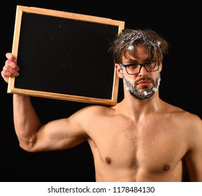 Need take shower. Man sexy muscular torso naked body hold blackboard copy space. Macho attractive nude guy show blackboard. Man bearded tousled hair covered with foam wears eyeglasses. Lack of water.