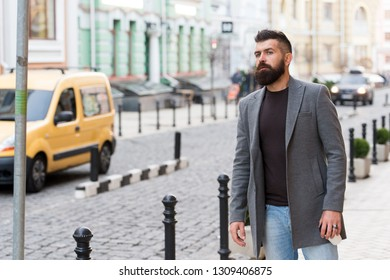 Need a taxi. Businessman catching taxi while standing outdoors urban background. Man bearded hipster casual style waiting for taxi. Guy at street city center. Looking for transportation. Bus stop.