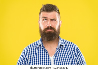 Need to think. Man serious face raising eyebrow not confident. Have some doubts. Hipster bearded face not sure in something. Doubtful bearded man on yellow background close up. Doubtful expression.