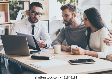 I need your signature here. Confident young man in shirt and tie holding some document and pointing it while sitting together with young couple at the desk in office