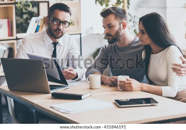 Ich brauche Ihre Unterschrift hier. Zuversichtliche junge Mann in Hemd und Krawatte, die ein Dokument hält und es beim Zusammensitzen mit einem jungen Paar im Büro anzeigt