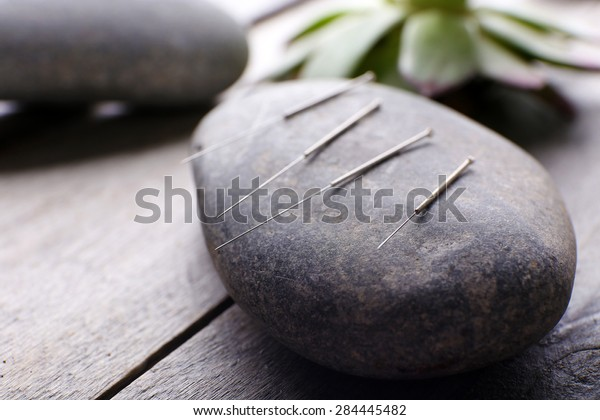 Nadel für Akupunktur auf Kursteinen auf Tisch, Nahaufnahme