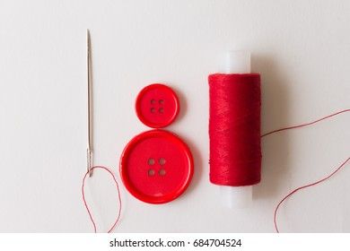 Needle, buttons and red thread on a white background. Business and hobbies. Needlework.