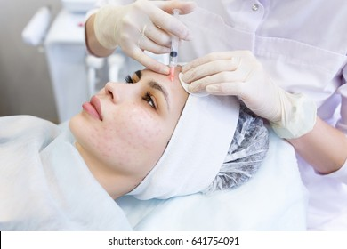 Needle mesotherapy in beauty spa salon or clinic. Cosmetologist inject to woman's face botox and collagen
