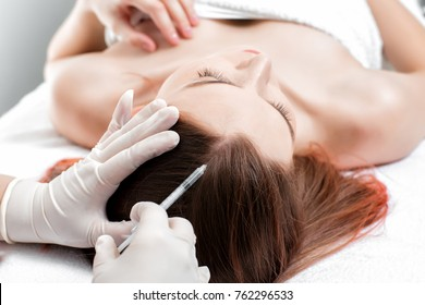 Needle mesotherapy. cosmetologist makes injections in woman head. strengthen the hair and their growth