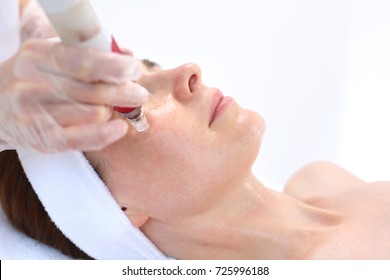 Needle mesotherapy treatment aesthetic execution in the beauty salon. Beautician performs a needle mesotherapy treatment on a woman's face