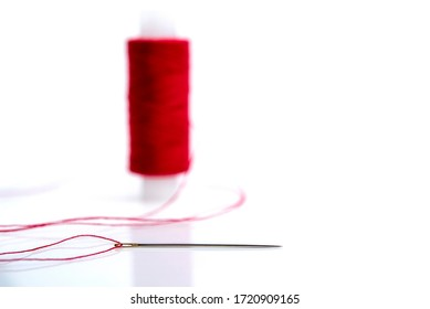 needle with red thread on the background of a spool of thread, horizontal photo