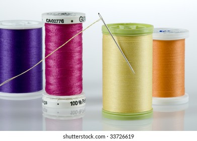 Needle stuck in yellow spool, surrounded by purple, pink and orange thread.