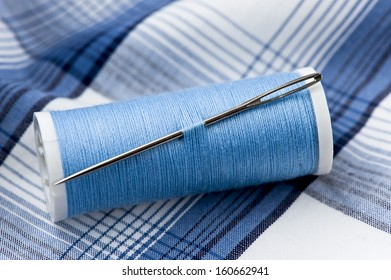 needle and thread on blue and white cotton material