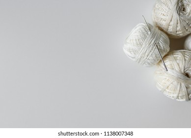 Needle and thread for sewing on white background. Top view of beige cotton yarn balls.
