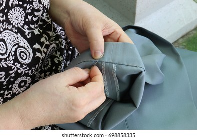Needle woman is sewing by hand