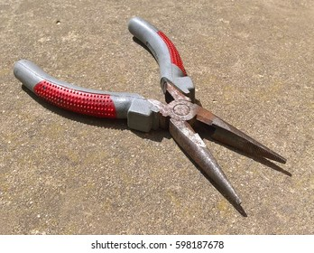 Needle-Nose Pliers Used. Open jaws and pivot point of red gray Needle-Nose Pliers. Concrete pathwalk in the background.