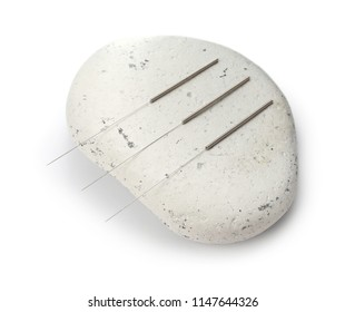 Needles for acupuncture and stone on white background