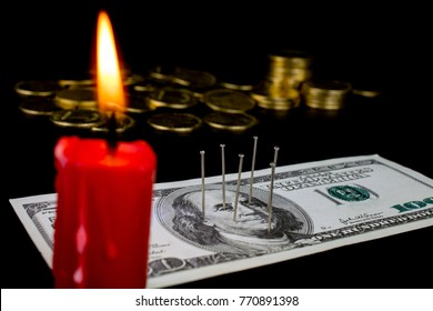 needles stuck in a dollar bill voodoo ritual, red candle, smoke and fire, gold coins, close up selective focus, dark background, concept the causes of the global financial crisis