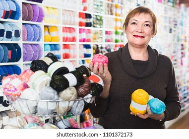 Needlewoman is buying colorful yarn for their hobby in needlework shop.