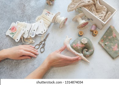 needlewoman hands make a snail rag toy, the entourage of a sewing workshop