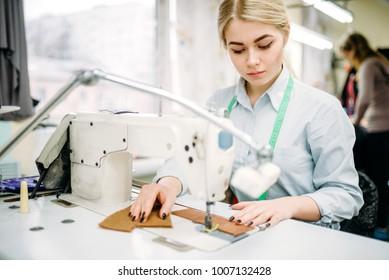 Needlewoman sews fabrics on a sewing machine