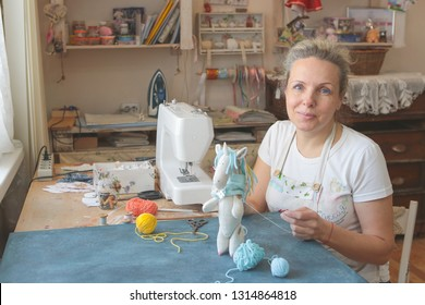 needlewoman in the workshop makes a toy rag unicorn